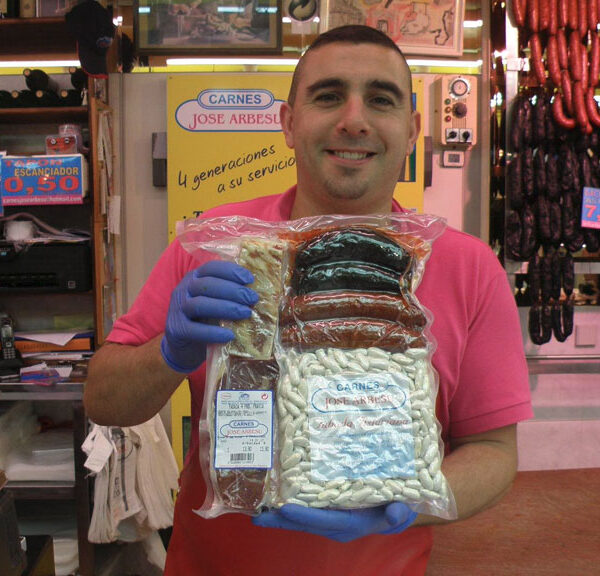En la carnicería José Arbesu posan con un pack para hacer fabada
