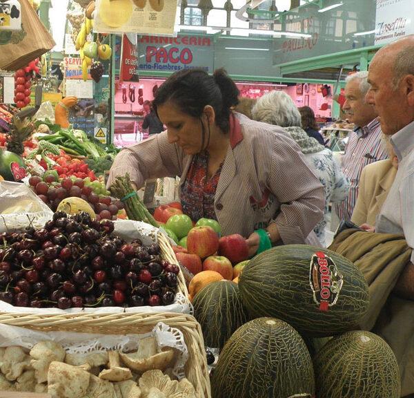 Un grupo de clientes espera a ser atendido en una de las fruterías del Mercado El Fontán