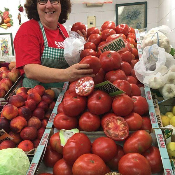 La frutera de Verduras Tomás posa rodeada de tomate asturiano