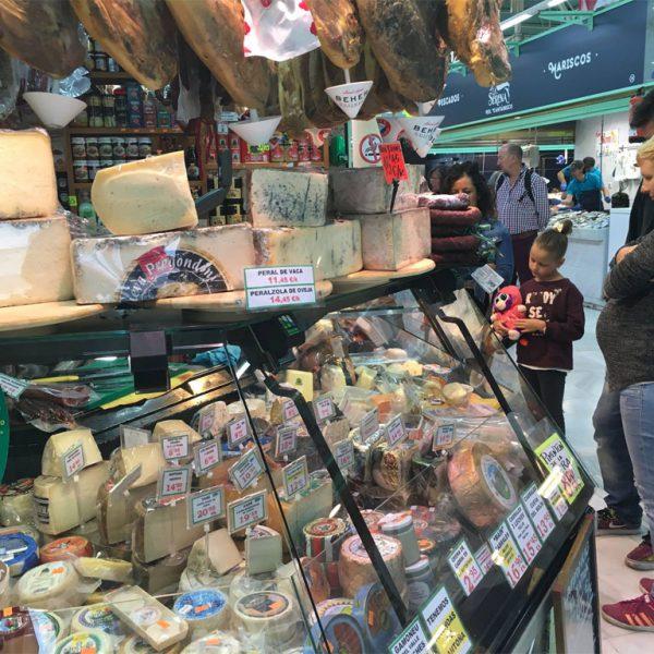 Una familia espera a ser atendida en uno de los puestos de Mercado El Fontán
