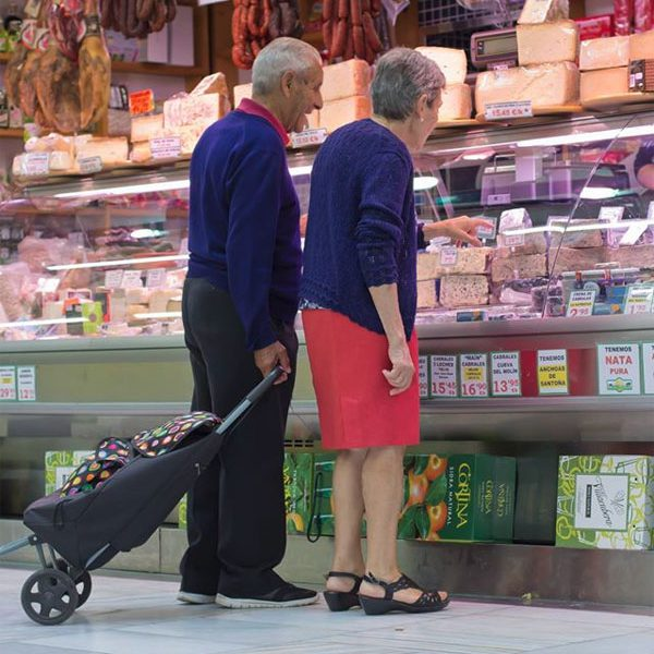 Un par de clientes son atendidos en un puesto de venta de quesos
